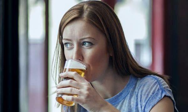 Женщина пьет пиво из бокала