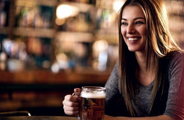 Барышня в баре собирается пить пиво